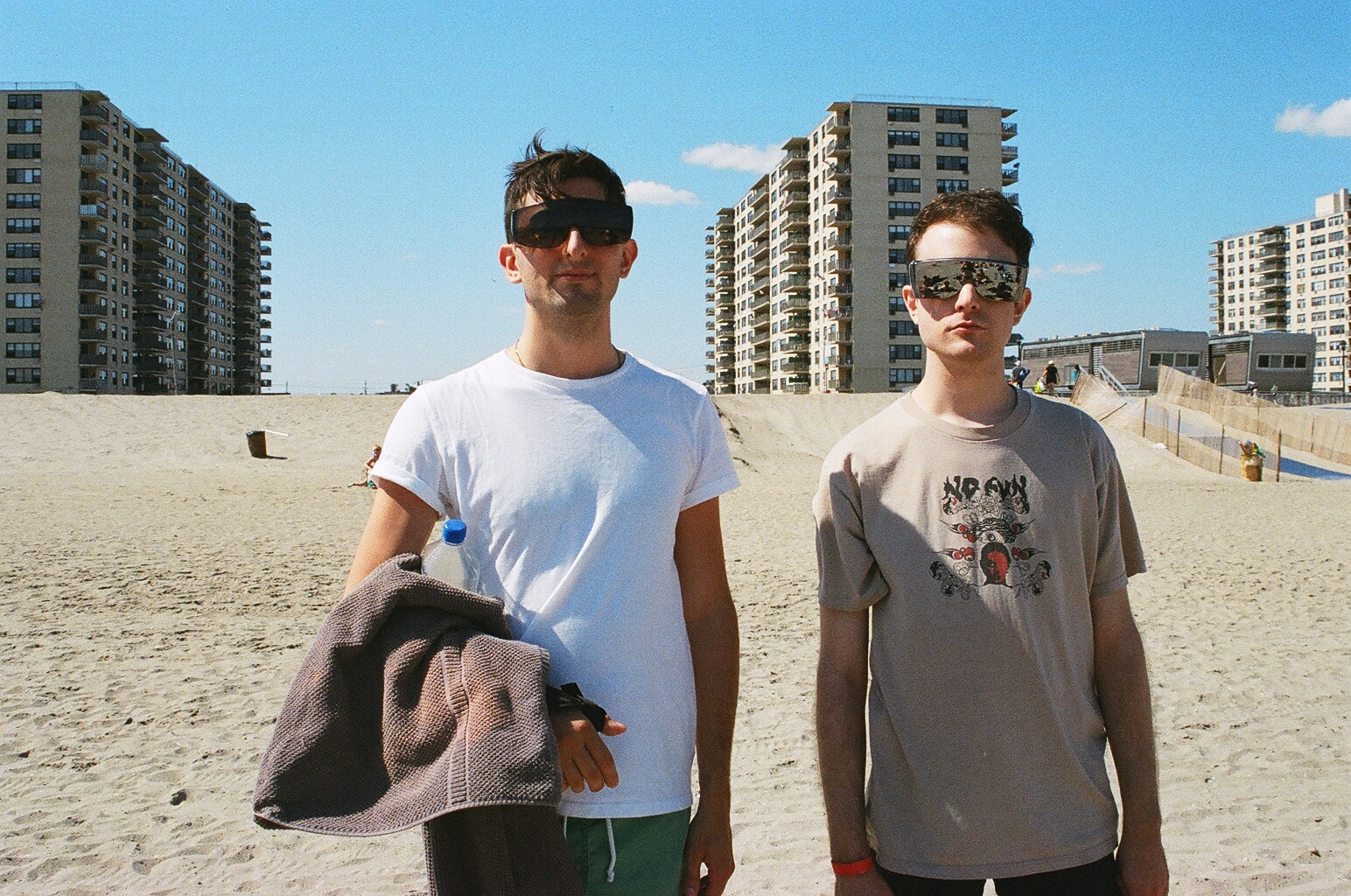 Josh + Party Tom in matching shades in front of the lovely ghetto by the sea.